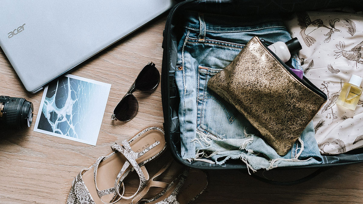 Open suitcase with camera, sunglasses, and laptop