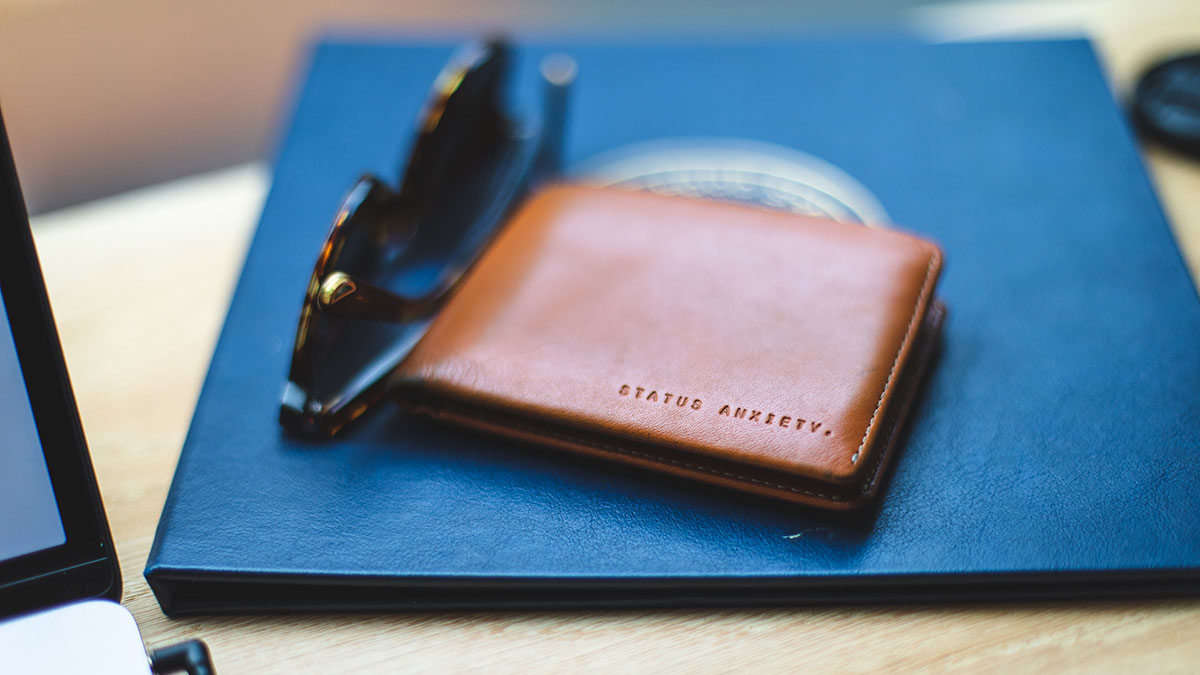 Wallet sitting on table next to sunglasses