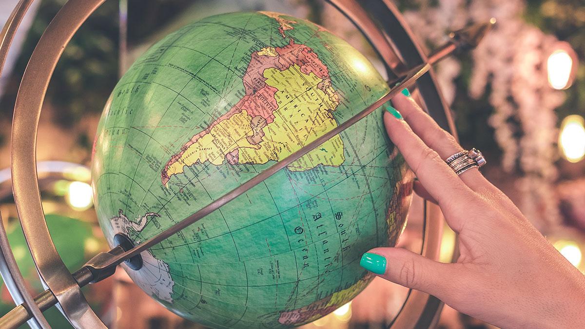 woman's hand on globe