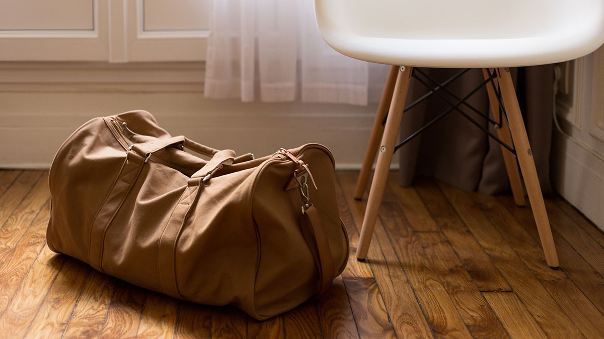 Brown duffel bag on floor next to a chair